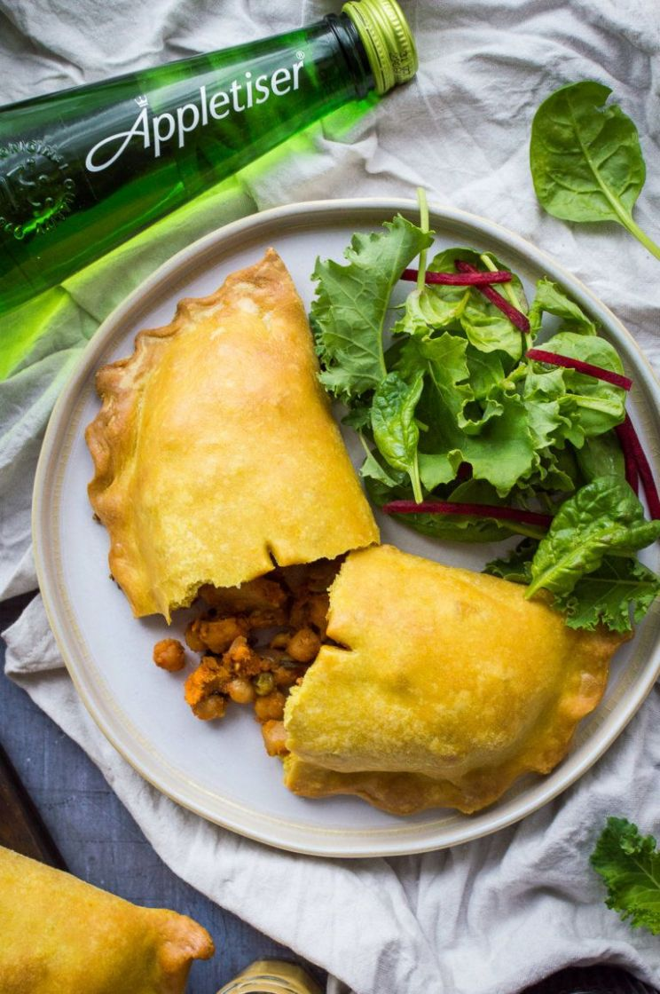 Close up of a vegan curried vegetable pasty with salad and a ..
